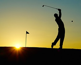golfer tees off at sunrise