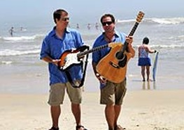 two male musicians holding guitars on the beach